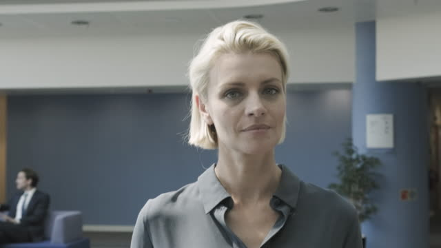 successful business woman executive walking in modern office lobby and looking into camera confident - authority bildbanksvideor och videomaterial från bakom kulisserna