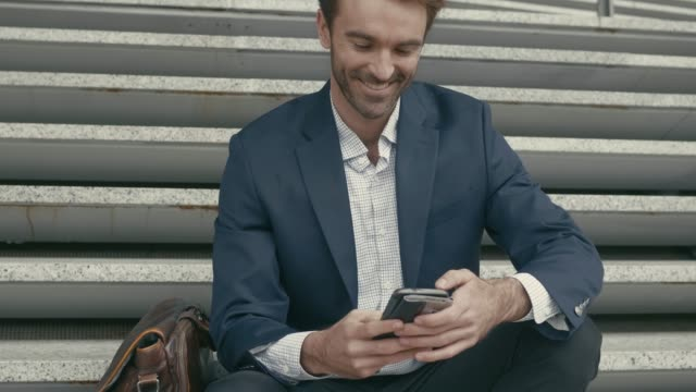 Successful businessman checking his mobile phone in the street