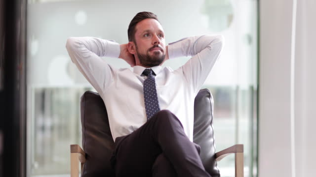 successful businessman leaning back in chair - cross legged stock videos & royalty-free footage