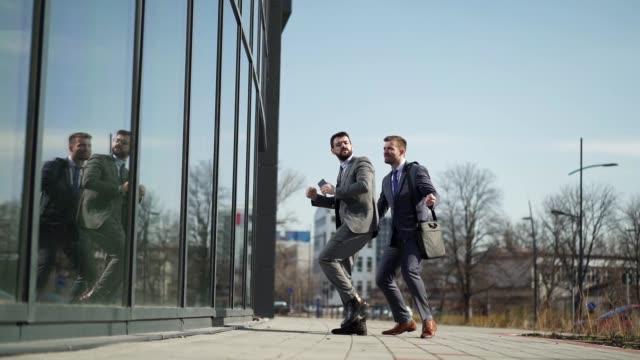 vidéos et rushes de l'homme d'affaires réussi exécutant célébrer la danse dans la rue après avoir fait une affaire avec la grande compagnie - collègue