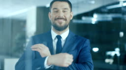 Successful Businessman Standing in the Office Smiles and Crosses Arms.