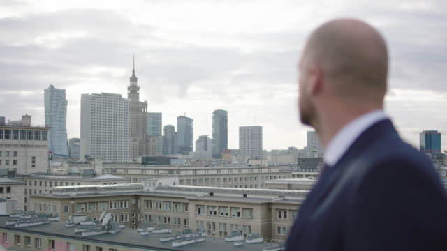 successful businessman walking on roof. admiring the view - panoramic stock videos & royalty-free footage