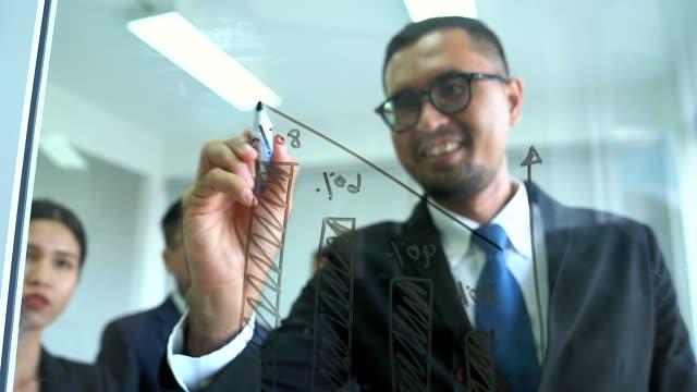 Los empresarios exitosos dibujan gráficos en el tablero de presentación de vidrio. El líder empresario que escribe en la pizarra presenta el gráfico de Marketing empresarial mientras se reúne con colegas en la oficina.