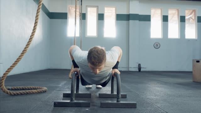 Succesvolle, zelfverzekerde man doen push-ups op de sportschool.