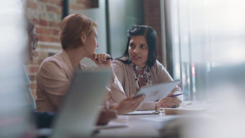 successful diverse businesswomen examine and discuss imporatant documents during a meeting - white collar worker stock videos & royalty-free footage