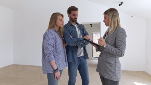 successful female realtor showing an empty apartment for rent to a young married couple - tenant stock videos & royalty-free footage