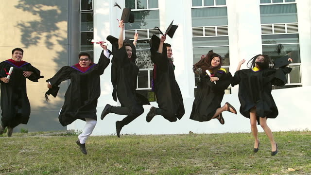 successful graduates in academic dresses are holding diplomas, looking at camera and smiling while jumping for the photo outdoors. - cap stock videos & royalty-free footage