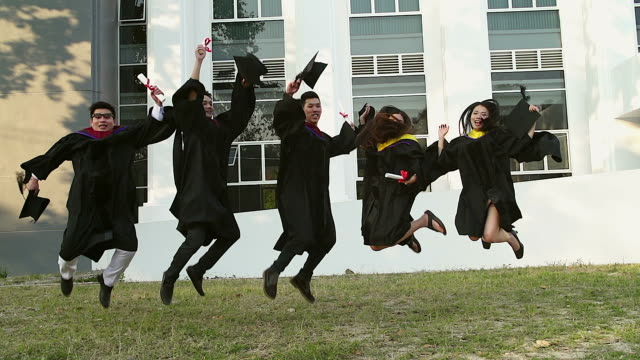 successful graduates in academic dresses are holding diplomas, looking at camera and smiling while jumping for the photo outdoors. - cap hat stock videos & royalty-free footage