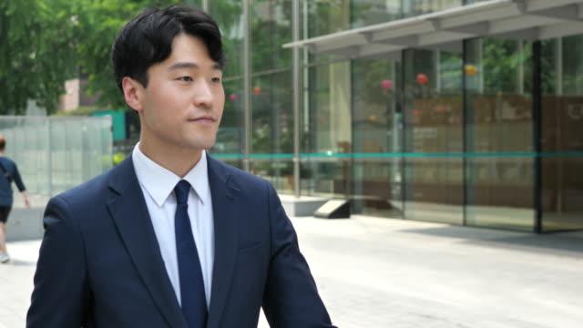 vidéos et rushes de homme d'affaires coréen réussi près de l'immeuble de bureaux - costume complet