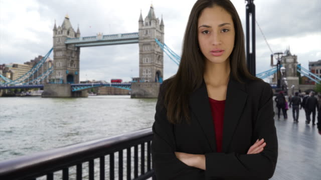 Successful Latina female on business trip stands near Tower Bridge