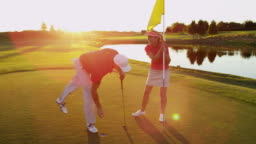 Successful male golfer female caddy winning game sunset