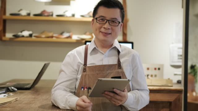 successful male taiwanese shoe merchant with digital tablet - retail occupation stock videos & royalty-free footage
