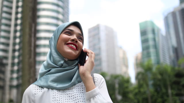 successful muslim businesswoman on cheerful phone call - telecommunications equipment stock videos & royalty-free footage