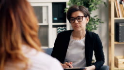Successful psychologist consulting female patient in office talking writing