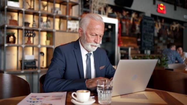 カフェでリラックスしながら仕事をしている成功したシニアビジネスマン - 最高経営責任者点の映像素材/bロール