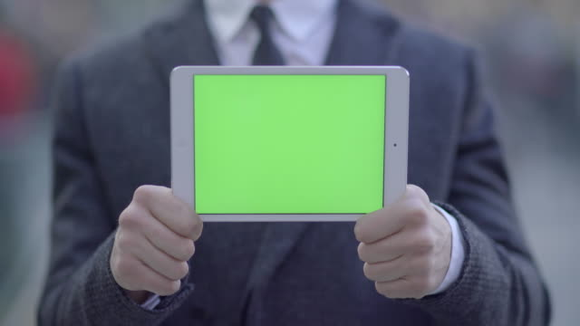 successful young caucasian business professional searching the web on tablet pc. green screen background