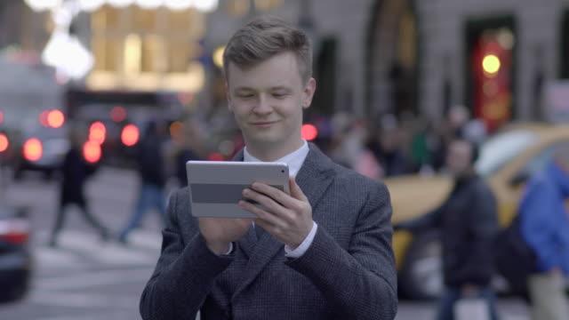 vídeos de stock, filmes e b-roll de successful young caucasian business professional searching the web on tablet pc in public place - camisa e gravata