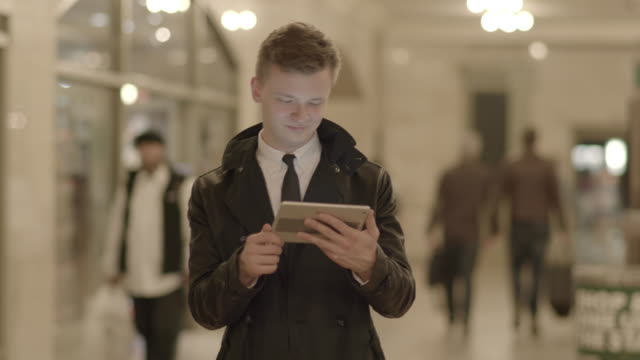 successful young caucasian business professional searching the web on tablet pc in public place