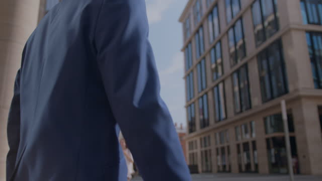 a successful young man in a business suit is walking down the street on a sunny day. the camera moving behind the man, shooting it from the back. he has built a company that makes sales hundreds of times more than its competitors! - full suit stock videos & royalty-free footage