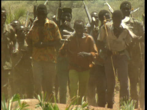 vídeos de stock, filmes e b-roll de sudan peoples' liberation army soldiers some with weapons dancing and marching on dusty ground - sudão