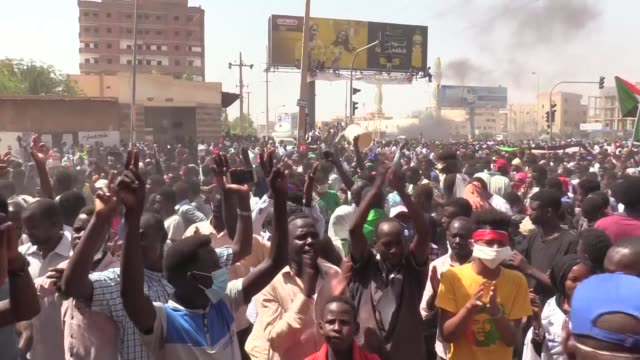 vídeos de stock, filmes e b-roll de sudanese demonstrators lift banners and national flags while smoke billows from burning tyres during a protest on sixty street in the east of the... - sudão