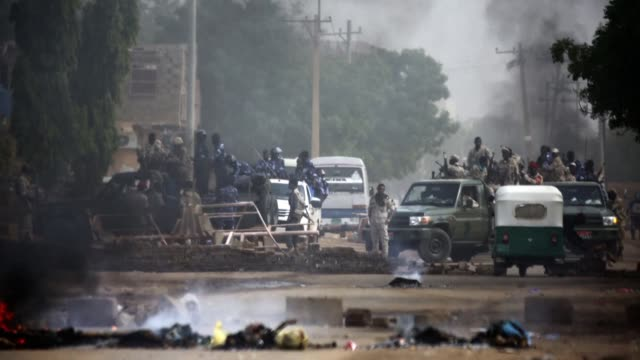 vídeos de stock, filmes e b-roll de sudanese protesters block a street with paving stones and burning tyres as sudanese forces are deployed at the protest site in khartoum - sudão