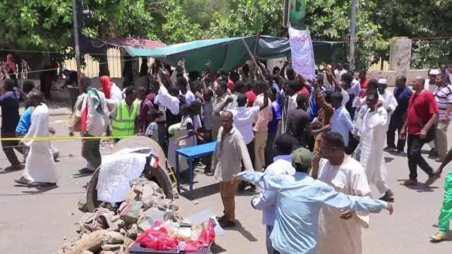 vídeos de stock, filmes e b-roll de sudanese protesters cross roadblocks and barricades to reach a sit in outside the army's headquarters in khartoum as tensions mounted over the makeup... - barricada divisa
