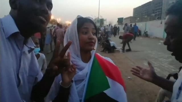 vídeos de stock, filmes e b-roll de sudanese protestors shout slogans and wave their national flag during the fifth night of a defiant sit in calling for president omar al bashir to... - sudão