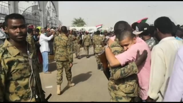 vídeos de stock, filmes e b-roll de sudanese soldiers hug and shake hands with demonstrators outside the army hq as they protest and await an important announcement from the military - sudão