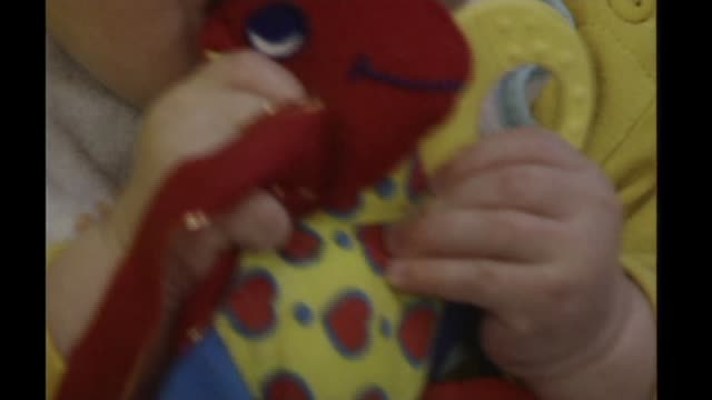 New study links cot deaths to gene defect INT Mobile rotating over child's cot Anonymous close shots of baby with soft toy Anonymous shot of baby...