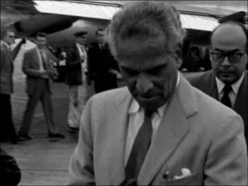 stockvideo's en b-roll-footage met krishna menon arrives in london; england: london airport : ext krishna menon along from plane as speaks to reporter t/x 23.9.56 / 6.10pm - krishna menon