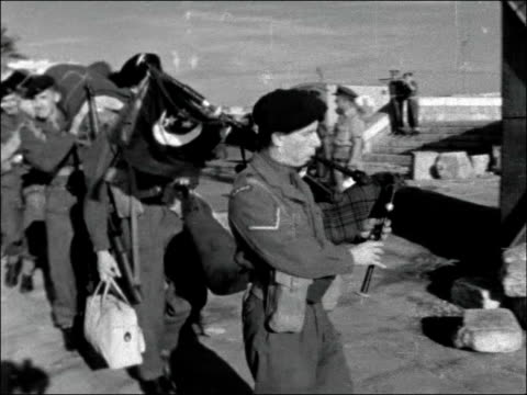 reservists leave port said for home; egypt: port said: ext gv troops towards camera with kit / ditto / bv on quay / troops towards led by piper /... - port said stock videos & royalty-free footage