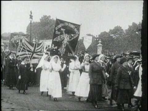 Suffragettes march with banners and a British flag