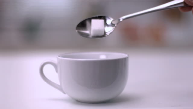 sugar cube falling from teaspoon into a white cup - teaspoon stock videos and b-roll footage
