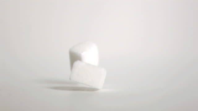 sugar cubes falling down in super slow motion - due oggetti video stock e b–roll