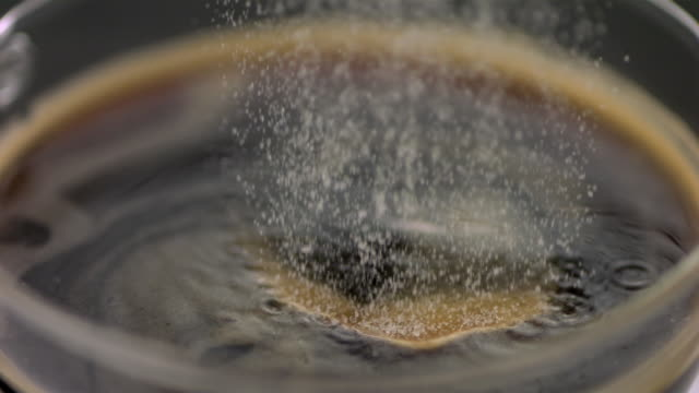 slo mo ecu sugar falling into coffee - brown stock videos & royalty-free footage