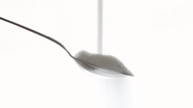 sugar falling on a spoon - sugar stock videos & royalty-free footage