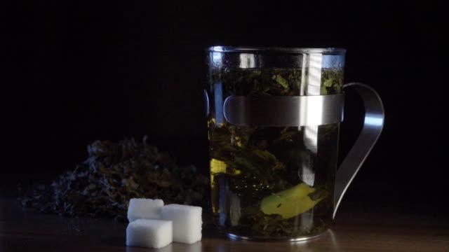 sugar falls in peppermint tea slowmotion - sugar cube stock videos & royalty-free footage