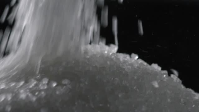 slomo sugar grains poured into mound, uk - sugar stock videos & royalty-free footage