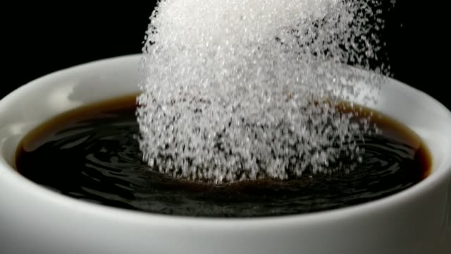 Sugar pouring into Black coffee - Close up