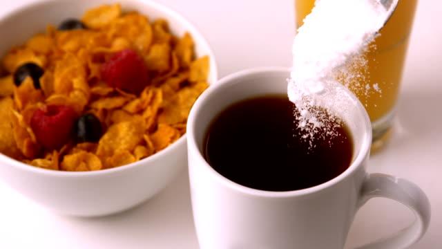Sugar pouring into mug at breakfast table