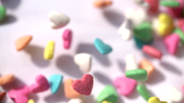 sugar small candy heart shape dancing on white background - lollipop stock videos & royalty-free footage