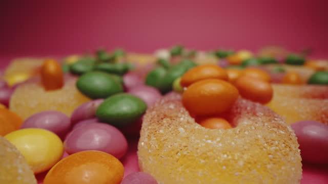 vídeos de stock e filmes b-roll de sugared gummy candies with a variation of  multicolored sour candies - coinfeitos