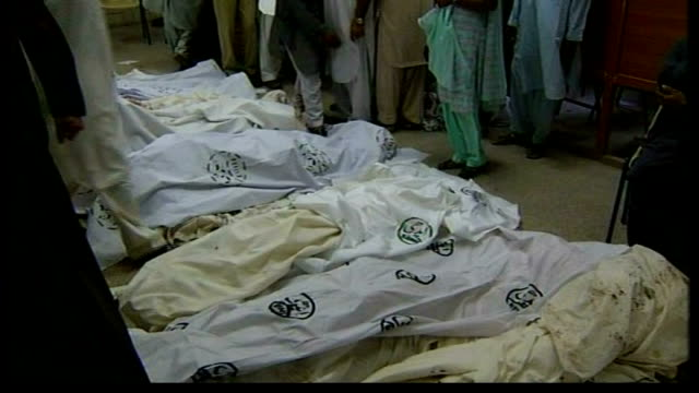 suicide attack on benazir bhutto's welcome convoy bodies of bomb attack victims lie covered with sheets on stretchers in mortuary corridor blood... - gory of dead people stock videos & royalty-free footage