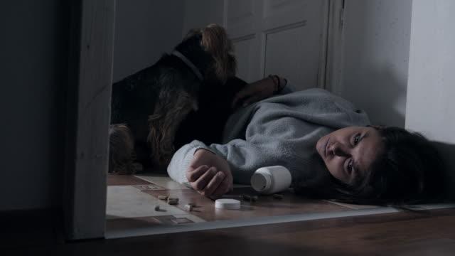 vidéos et rushes de femme de suicide à la maison, corps de femme posant dans le couloir à la maison avec des pillules dispersées autour - the human body