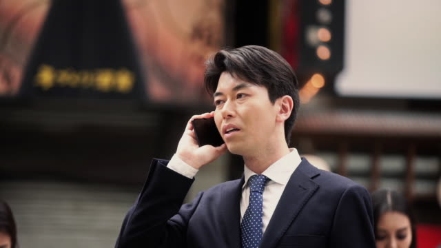 Suit Wearing Man Talking on Phone in Street