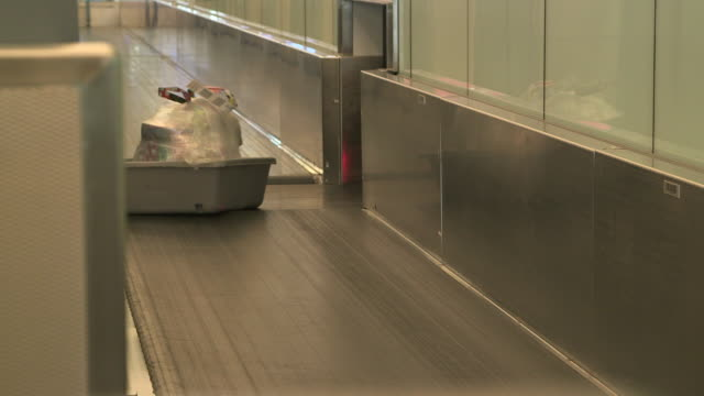 suitcase in security bin at airport - plastic bag stock videos & royalty-free footage