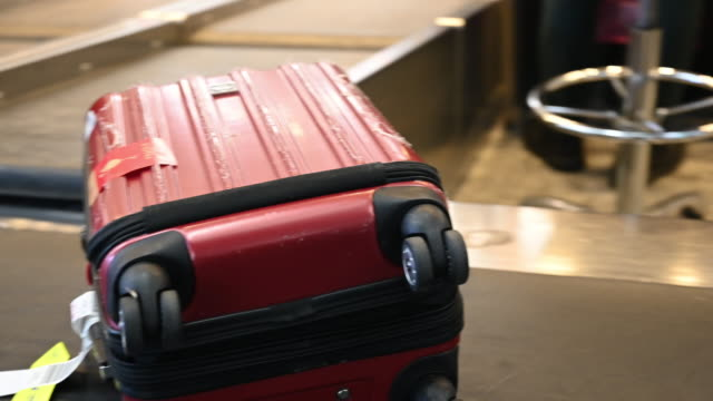 suitcase travelling on airport conveyor belt - wheeled luggage stock videos & royalty-free footage