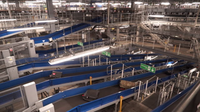 suitcases and luggage being transported through the baggage handling process on conveyor belts at heathrow airport - belt stock videos & royalty-free footage