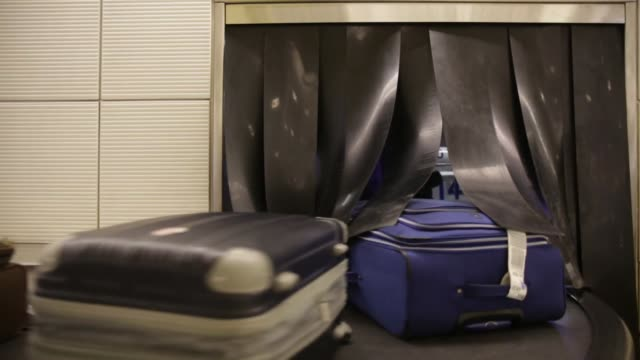 Suitcases move on a conveyor in the baggage claim area at onald Reagan National Airport in Washington DC US on Wednesday Nov 25 2015 Photographer...